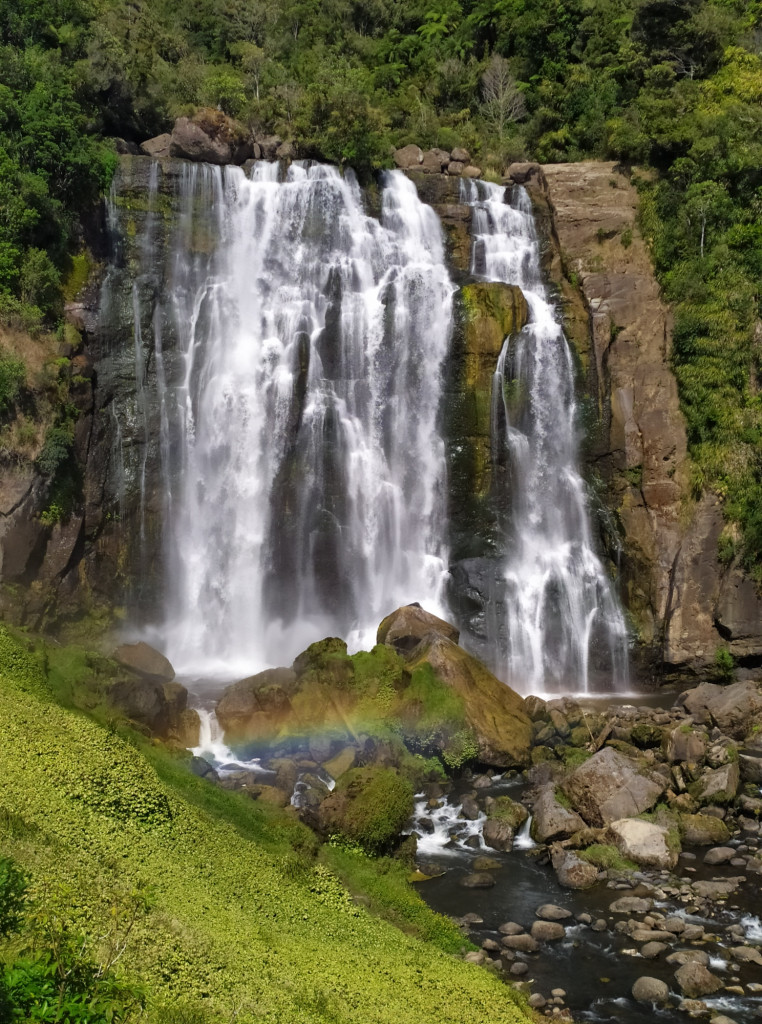 Suggestivo scatto di una cascata baciata da un arcobaleno, Isola del Nord, NZ.