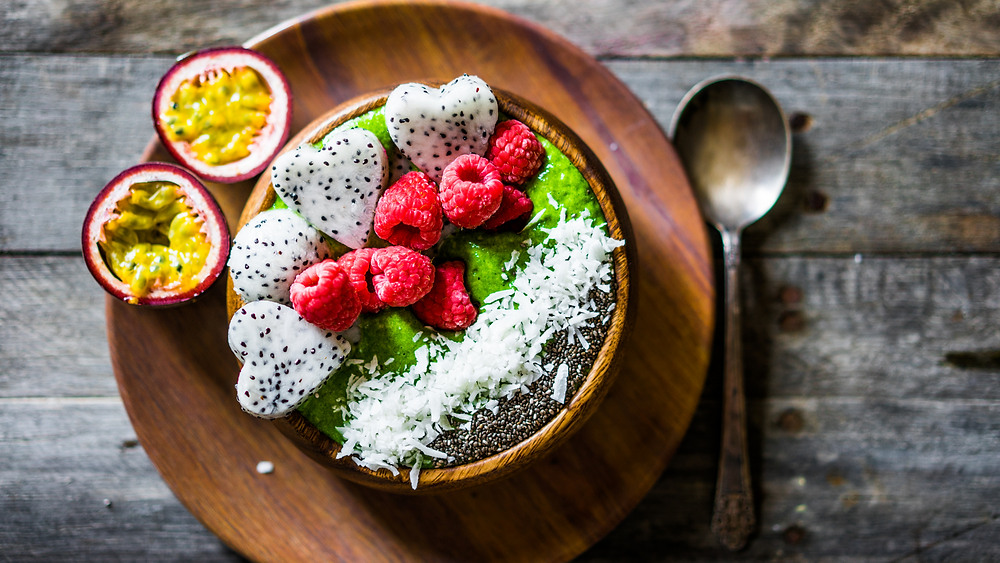 Ciotola ripiena di frutta su base cremosa verde. Una smoothie bowl ricca di colori contrastanti. Immagine presa dal web