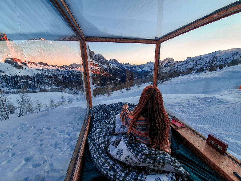 Risveglio nella stanza di vetro tra i versanti delle Dolomiti innevate.