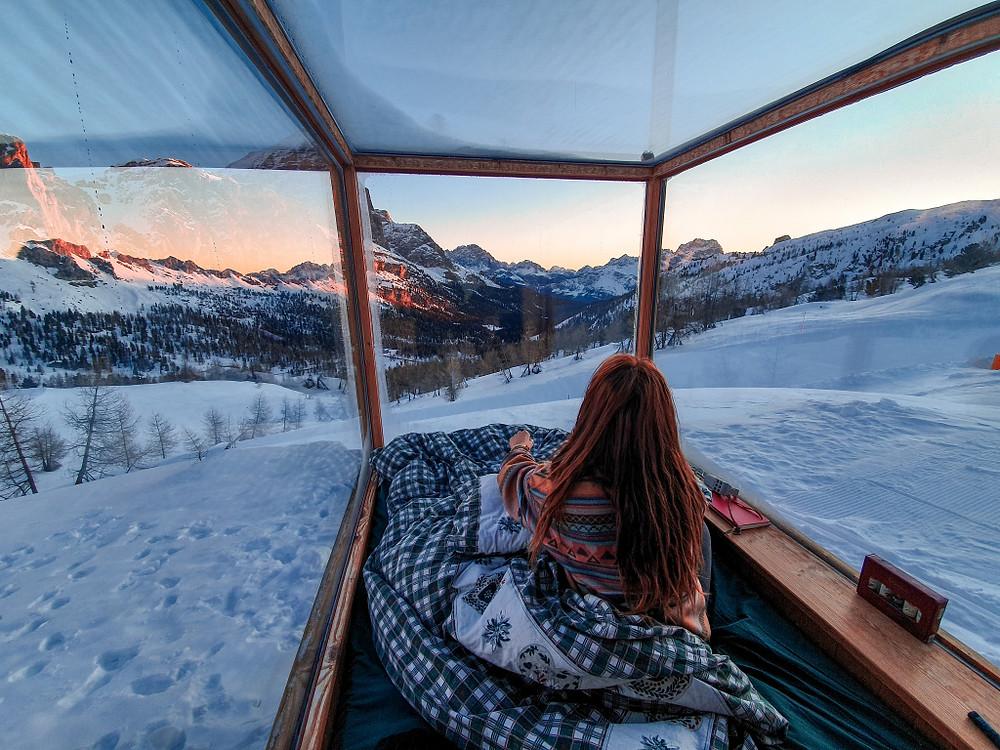 Un buongiorno di poche parole ma di mille colori. Io di spalle guardo le Dolomiti attraverso le pareti di vetro della camera in cui abbiamoa vuto il piacere di dormire. Starlight Dolomites Room. Il momento dell'alba.