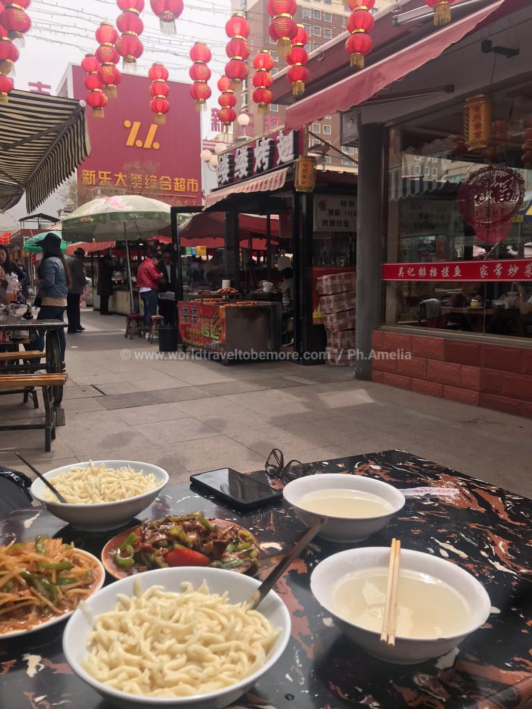 Primo piano della tavola pronta al pranzo, in sfondo un viale tradizionale, con colori e oggetti tipici della cultura cinese.