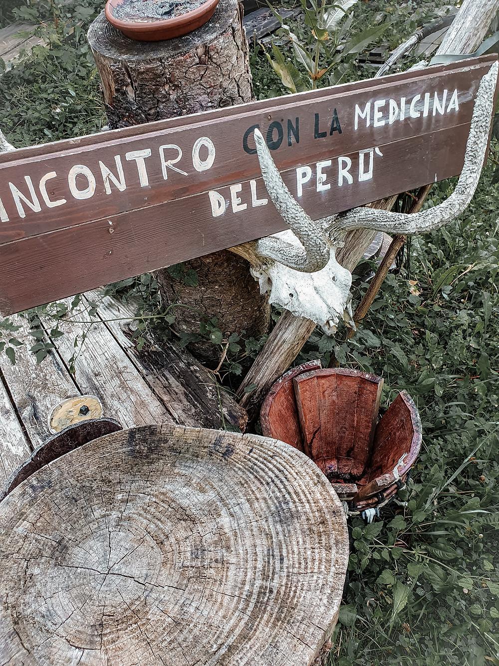 """Una frase a chiare lettere ci incita al sapere: """"Incontro con la medicina del Perù"""". L'asse di legno su cui è scritta è sostenuta dallo scheletro della testa di un animale. Nel villaggio indiano in Emilia Romagna, eccoci spiegata la medicina Peruviana."""