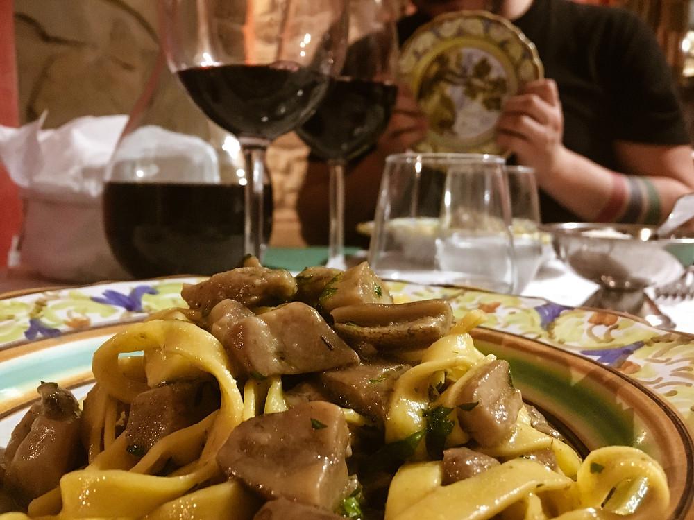 Tagliatelle ai funghi porcini raccolti in giornata. In sottofondo il piatto decorato a mano celebre della città di Castelli.
