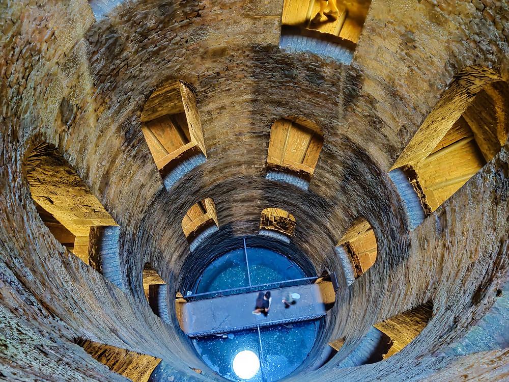 Pozzo di San Patrizio a pochi metri dal fondo. Il riflesso dell'acqua rende l'atmosfera magica! Lateralmente finestre stondate che dalle gradinate affacciano sul fondo del pozzo stesso. Orvieto