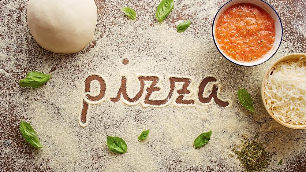 Fotografia degli ingredienti base per la pizza. Il nome è scritto nella farina, immagine presa dal web