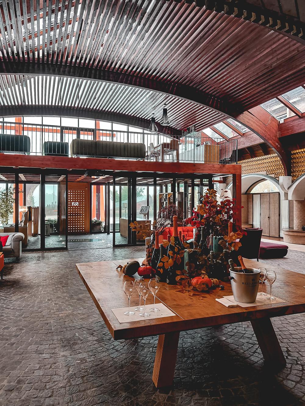 Sala d'accoglienza dell'azienda Bellavista durante il periodo autunnale. Sopra al tavolo in legno massiccio la bottiglie pronta per la degustazione con i relativi calici. Foto by Gajjey Travel to be more