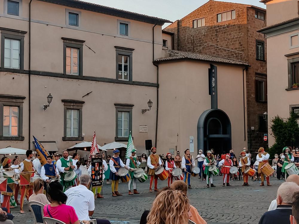 Piazza del Popolo, Orvieto. Un gruppo di sbandieratori, accompagnata da diversi musicisti, mette in scena uno spettacolo al tramonto.