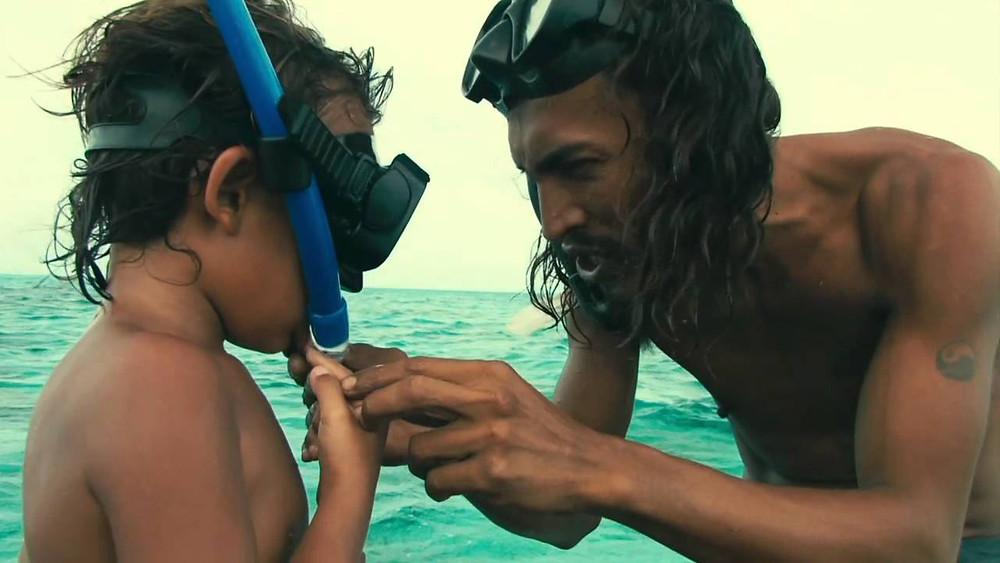 Il papà di Natan gli sistema il boccaglio per la prima immersione di snorkeling.