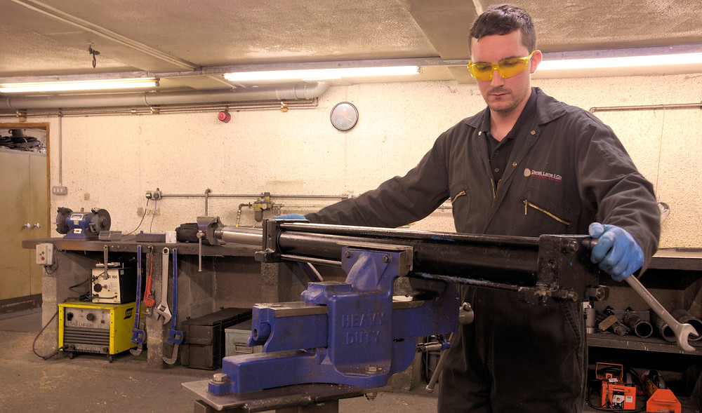 Engineer servicing a hydraulic cylinder at Derek Lane & Co: Hydraulic and Pneumatic Sales and Services in Exeter, Devon