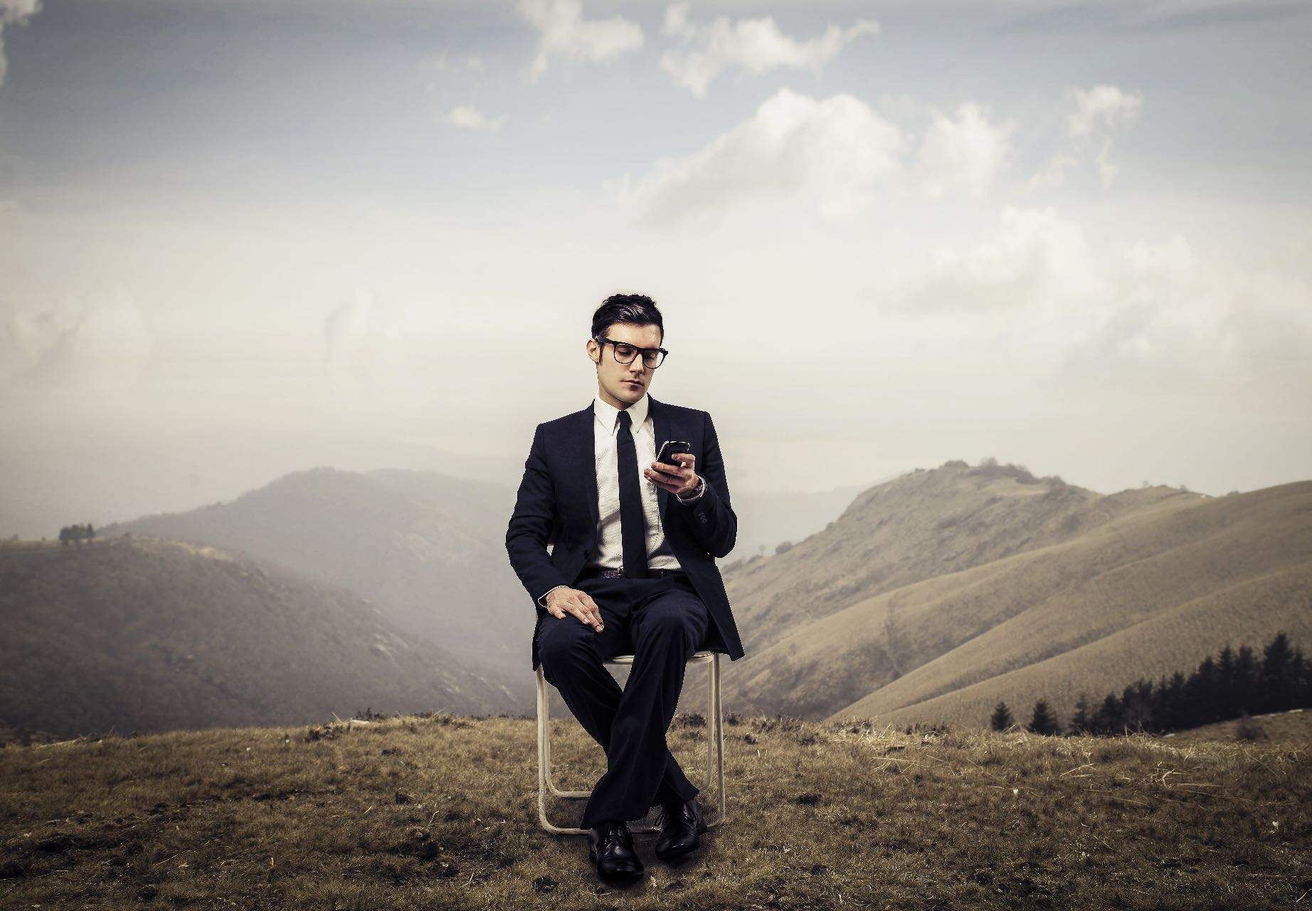 Business Man Using Phone on Mountain