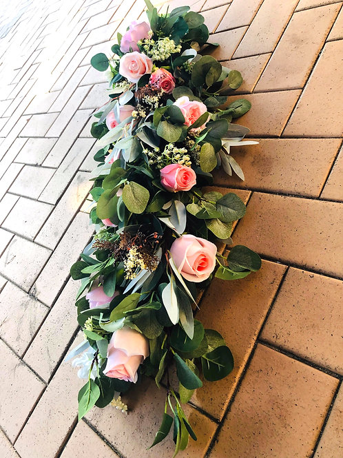 Greenery centerpiece garland with pink flowers.