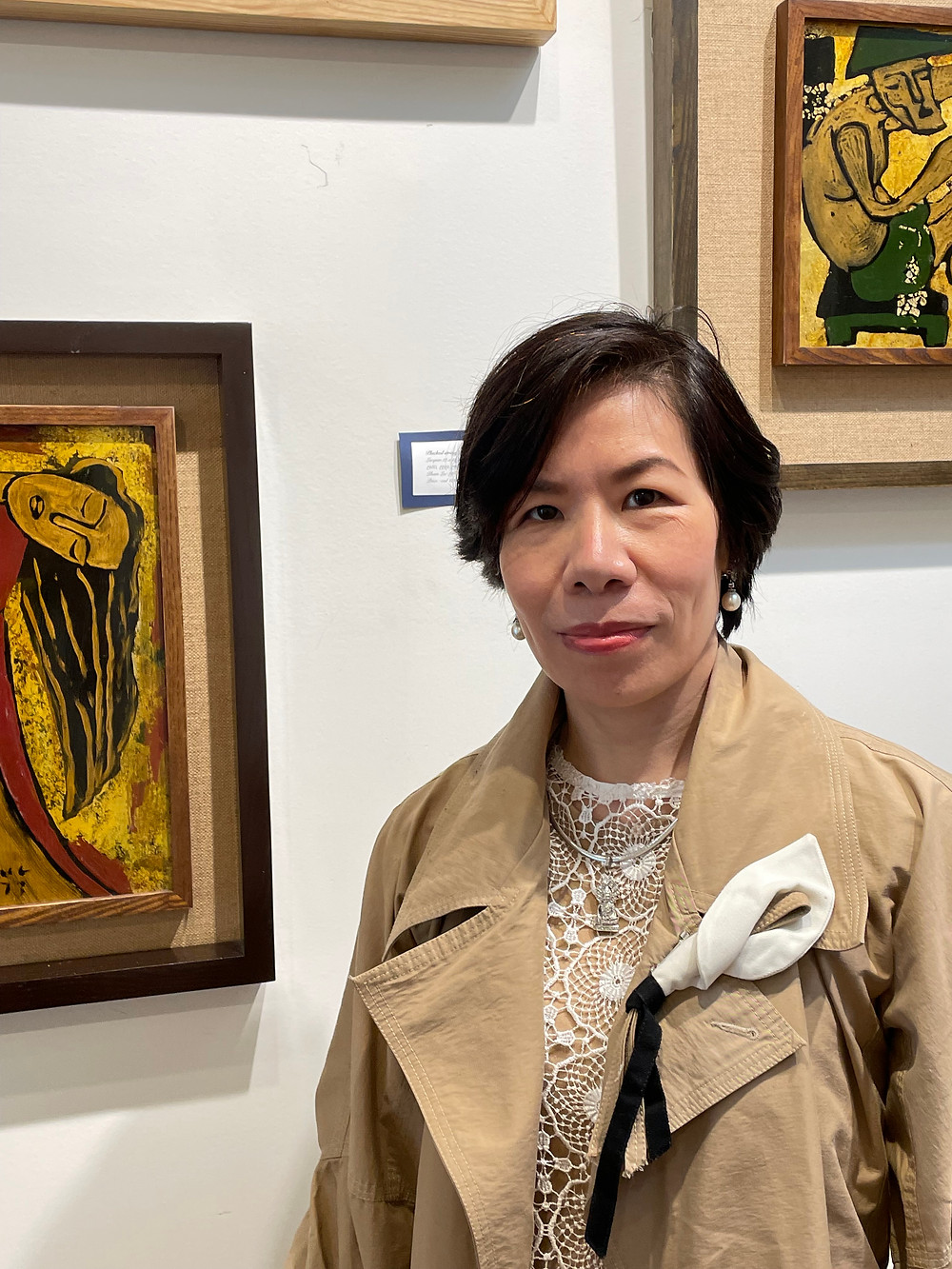 Julia Thieu stands in front of her art pieces. She wears a beige coat with a floral broach.