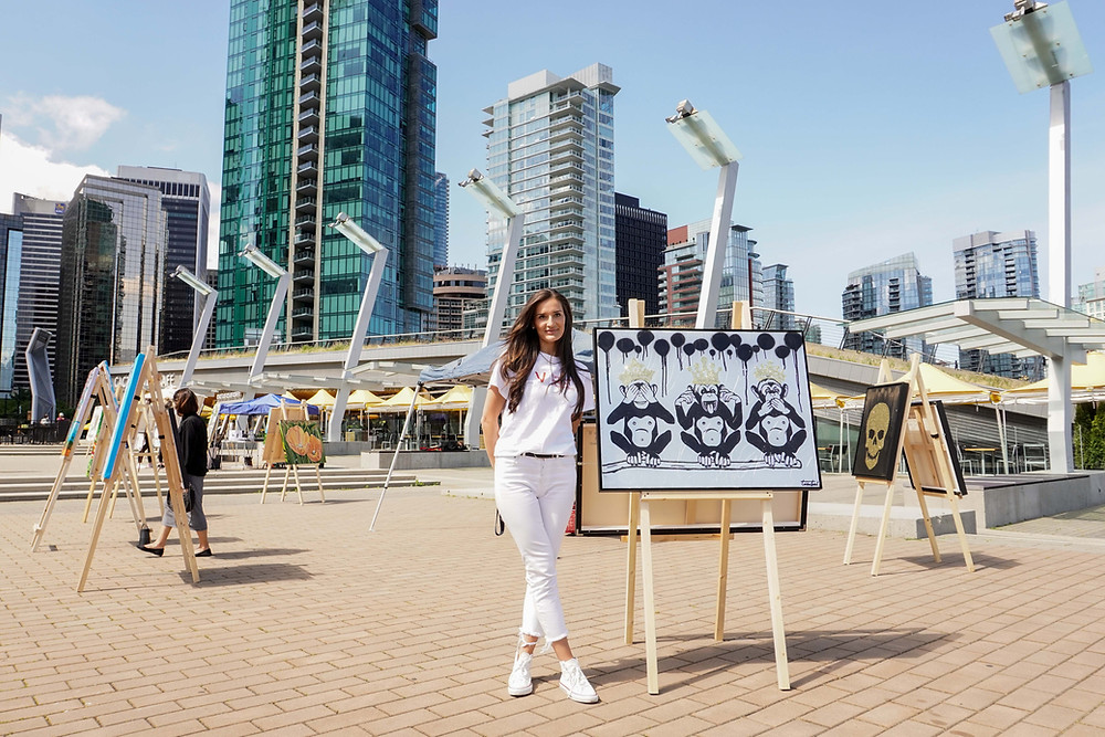 Artist stands beside easel with her painting of three monkeys. She is in a plaza with easels in the background, and a city scape further behind.
