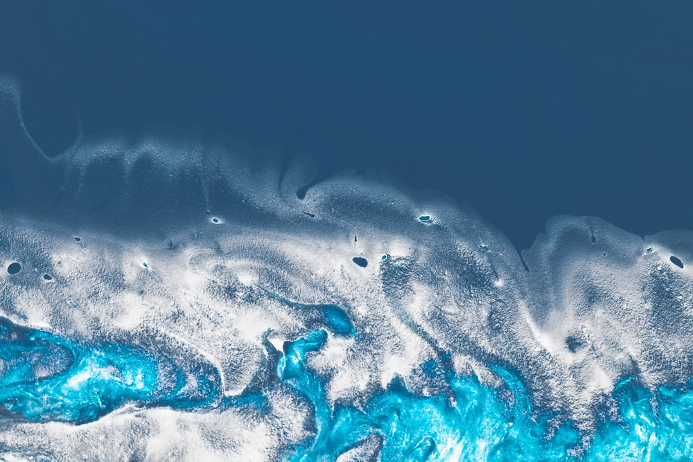 Image shows an abstract painting with various blues swirling into white ripples, appearing similar to an ocean wave from above.