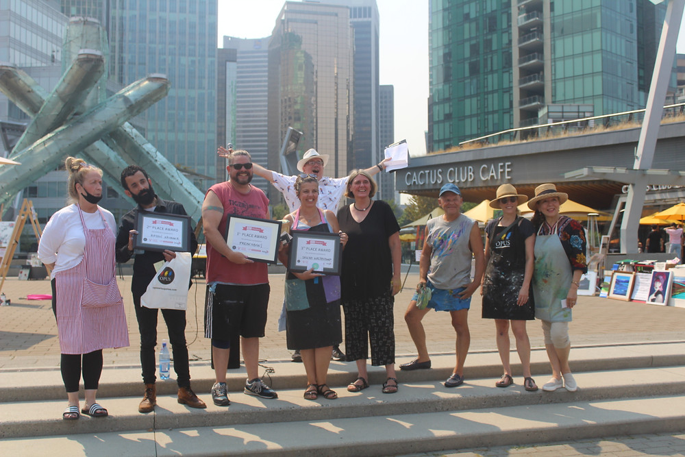A group of people stand on steps in the Jack Poole Plaza. 3 people hold their certificates with 1st, 2nd, 3rd place written on them. The rest smile holding their gift card prizes. The hazy city-scape glows in the afternoon sun behind them.