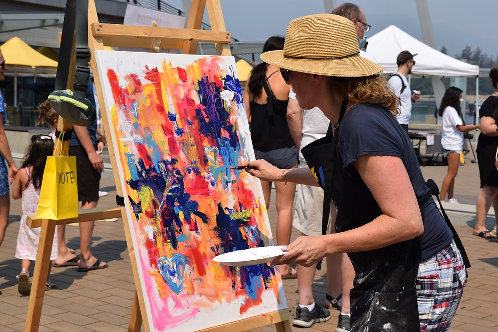 An artist works intensely on a coulourful piece of art, which sits on an easel among a sunny plaza.