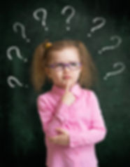 Child in eyeglasses standing near school blackboard with many question marks.jpg