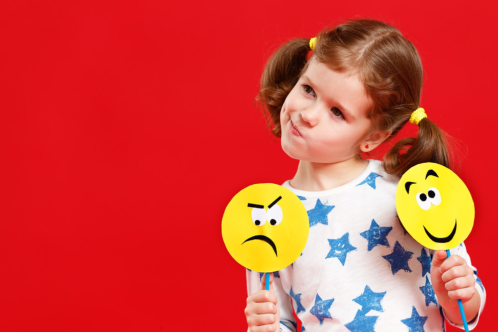 Girl with Happy and Sad Faces in Educational Therapy