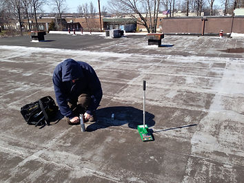 Roof service technician doing a core cut to check for wet insulation in the roof system