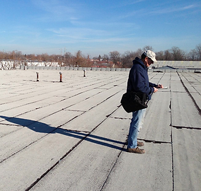 Service tech inspecting commercial flat roof