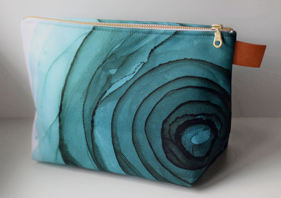 Image showing a large bag with a teal rose artwork design, a gold zipper and a brown pull tab.