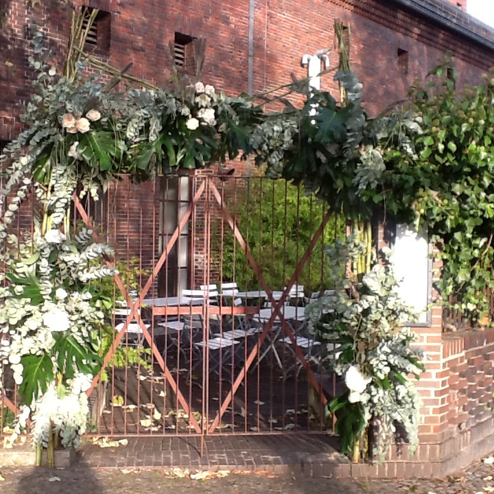 The entrance decorated with white flowers and green tropical leaves