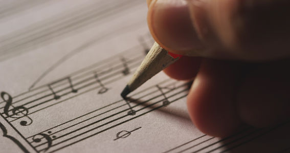 Macro close up of musician or composer hand writes a song or a musical work, writing notes