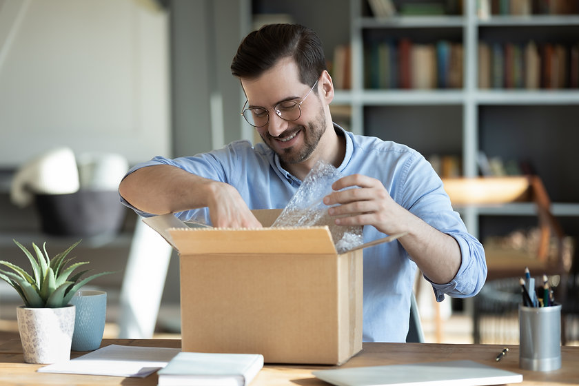 Smiling man wearing glasses unpacking aw