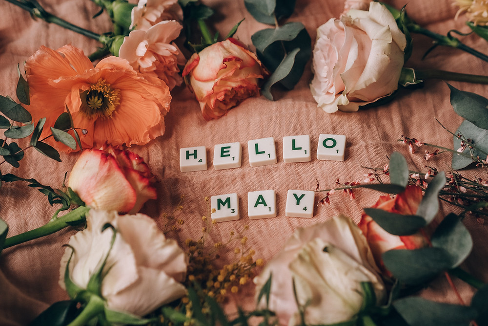 """Flowers surrounding tiles spelling """"Hello May"""""""