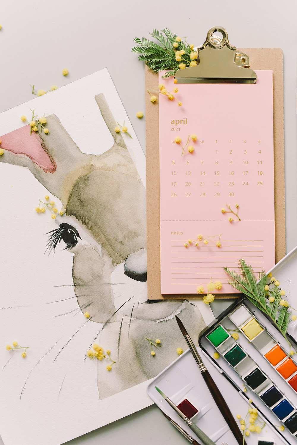 Bunny paining and april calendar on a clip board