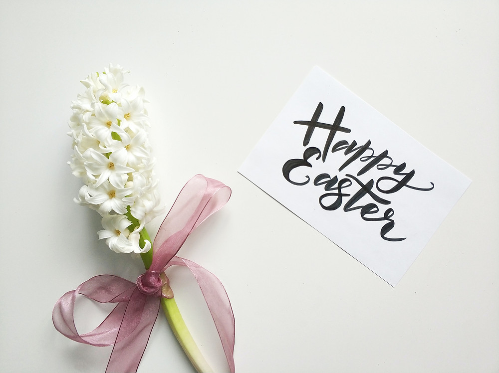"""Card saying """"Happy Easter"""" next to white flowers."""
