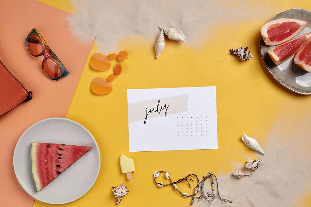 July calendar on yellow background surrounded by summer items (sea shells, sunglasses, watermelon, grapefruit & ice cream)