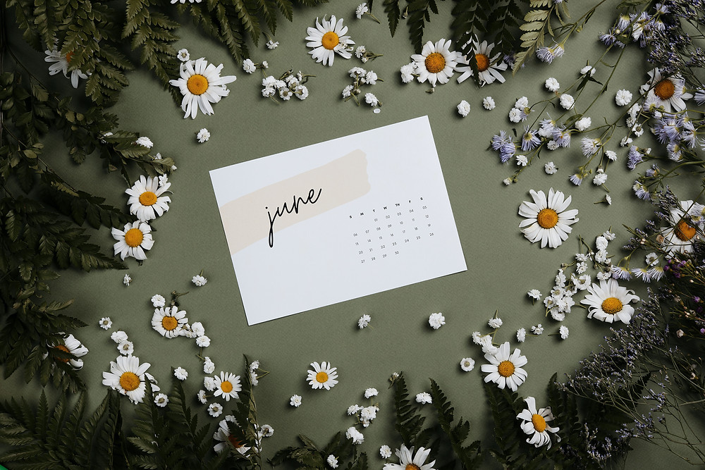 June Calendar surrounded by flowers on green background