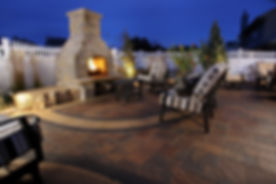 Custom paver patio with natural stone fireplace.