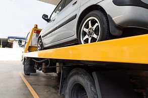 broken-car-on-flatbed-tow-truck-being-tr