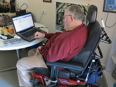 Man in wheelchair with cerebal palsy using laptop at home