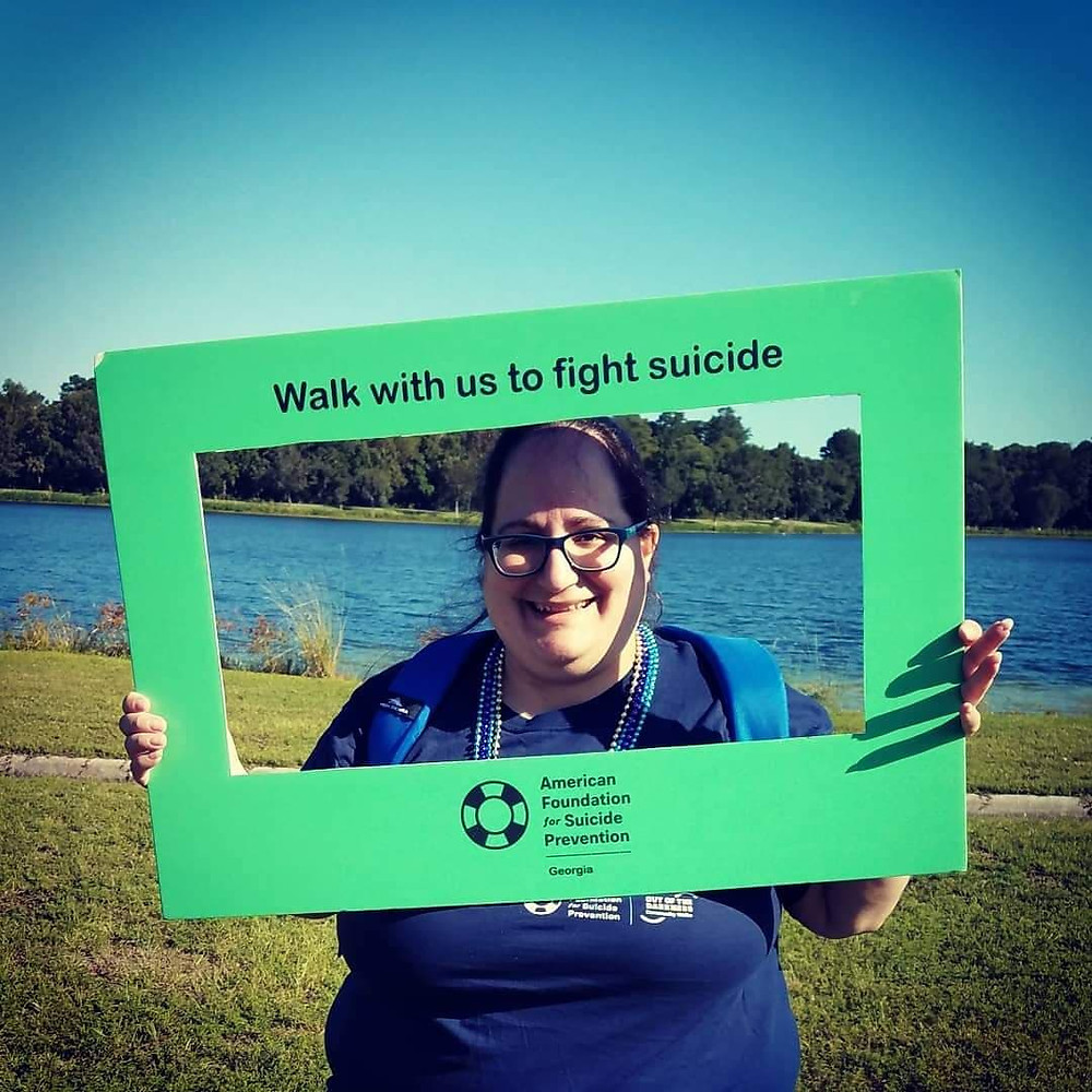 Nancy at Lake Mayer in Savannah Georgia holding sign that says Walk with us to fight suicide