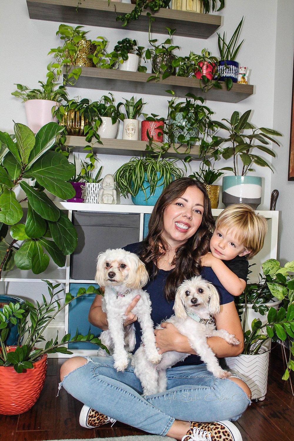 Background of potted plants on shelves with Sarah sitting on the floor holding 2 white fluffy dogs and her toddler son