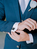 groom with film cufflinks blue suit