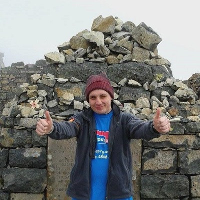 Joe in a red woollen hat, black jacket and Epilepsy Action t-shirt wit his thumbs up in front of the cairn on Ben Nevis.