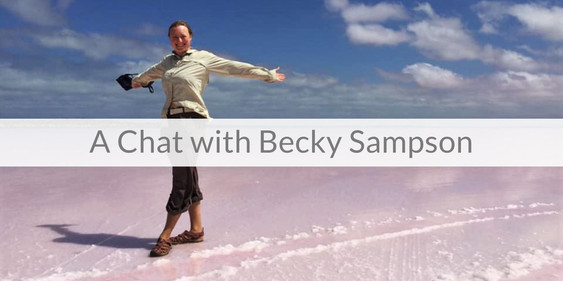BEcky standing on pink salt flats with blue sky. Her arms are out. Text reads 'A Chat with Becky Sampson'