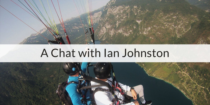 Shot from a Go-pro we see Ian and an insstructor tandem paragliding. There is a lake a mountains at a tilt, far below.