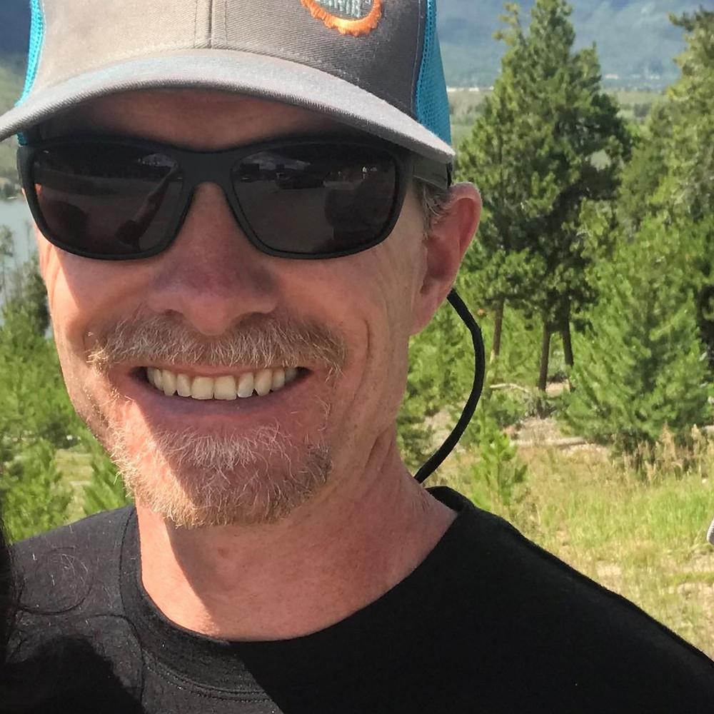 Smiling at the camera, Jake wears sunglasses and a baseball cap. Green trees behind.