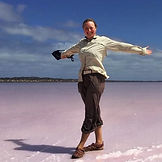 Becky Sampson on a pink salt flats, with her arms out wide