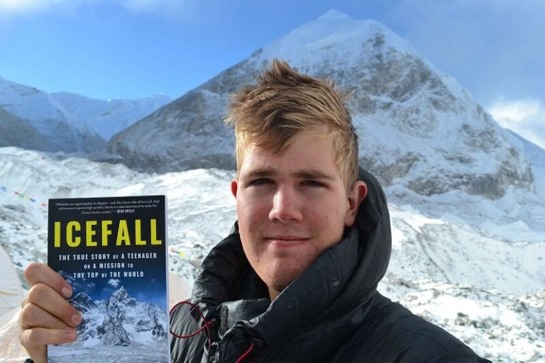 Alex Staniforth holding Icefall book in front of a mountain