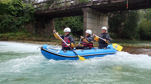 Ian's son, his wife and Ian are in an inflatable blue boat, paddling down a choppy river. There is a concrete bridge behind them.