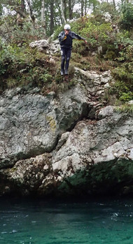 We can just about see Ian holding his nose as he jumps off a tall rocky cliff into the water at the bottom of the picture.