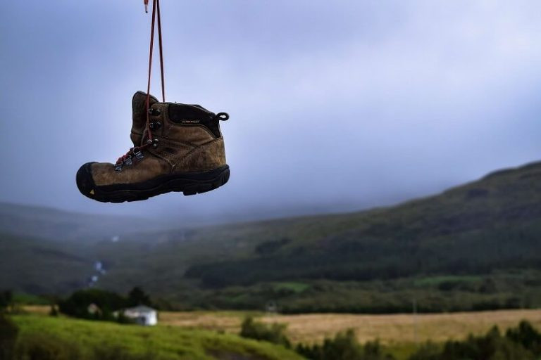 hiking boot hanging by laces in front of countryside rostyslav-savchyn-588215-unsplash