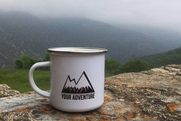 Seize Your Adventure enamel mug on wall with mountains by Francesca Turauskis