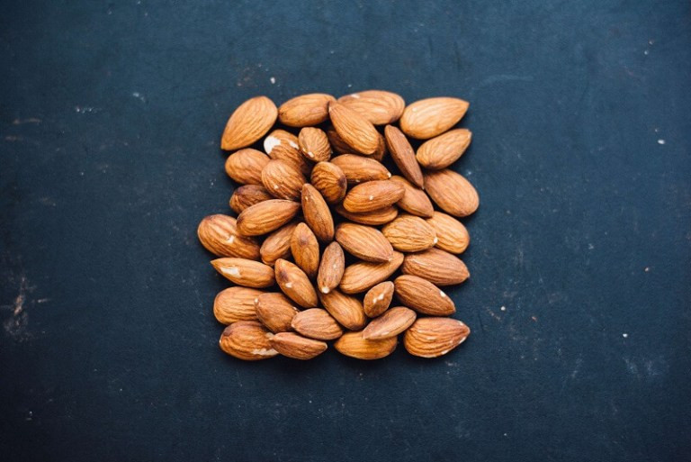 A square of almond nuts on a dark background
